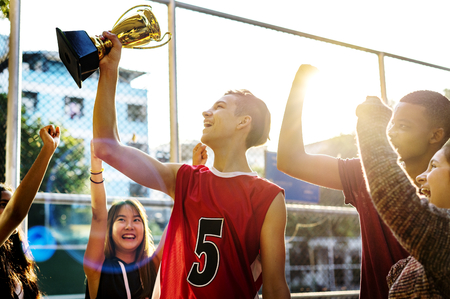 Group of teenagers cheering with trophy victory and teamwork concept Standard-Bild - 109714701