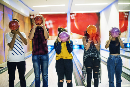 Friends playing bowling together indoors Фото со стока