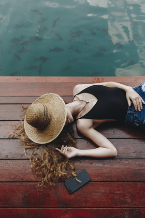 Woman relaxing on a wooden jetty Stock Photo