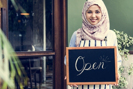 Muslim woman holding an open signage Banco de Imagens