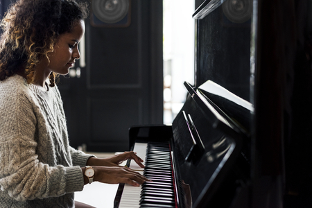Woman playing on a piano Stockfoto