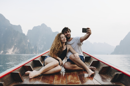 A lovely couple taking selfie on a longtail boat