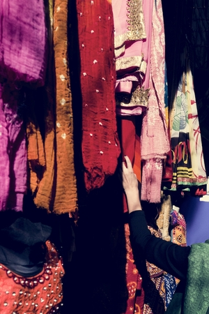 Woman choosing colorful sari in the market