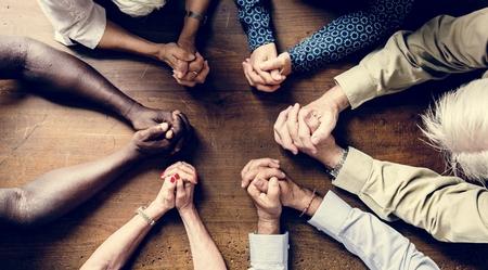 Groep met elkaar verbonden vingers die samen bidden