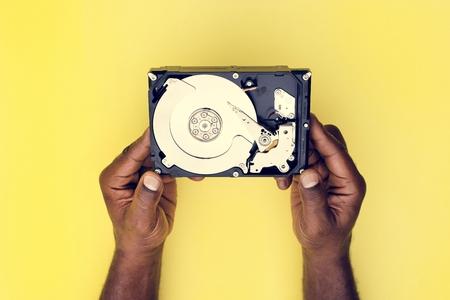 Manos sosteniendo la copia de seguridad de datos de la unidad de disco duro aislado en el fondo Foto de archivo