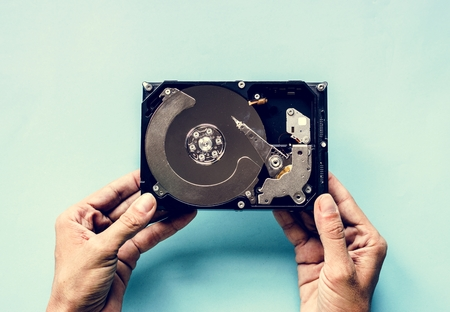 Hands holding HDD isolated on background