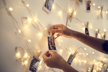 Close-up van habds met foto's die met decoratielichten op de witte muur hangen