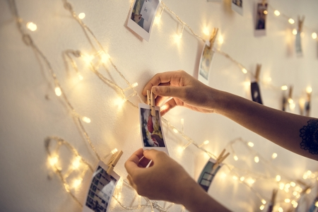 Closeup of habds with photos hanging with decoration lights on the white wall Stockfoto