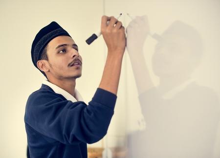 Muslim man writing on a white board