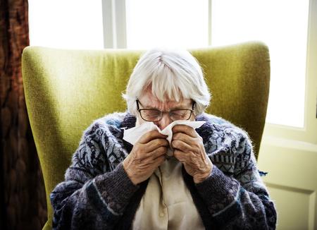 Senior woman sneezing Stock Photo