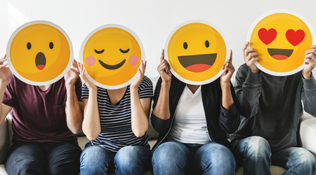 Diverse people holding emoticon Stok Fotoğraf