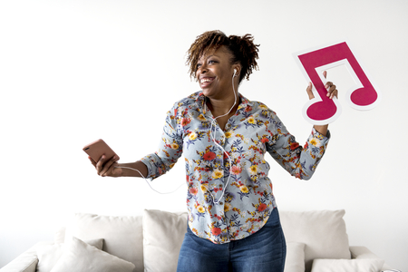 African American woman enjoying music at home holding musical note leisure and music concept