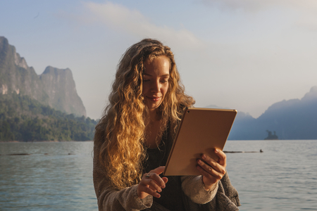 Woman using her tablet by a lake Stock Photo