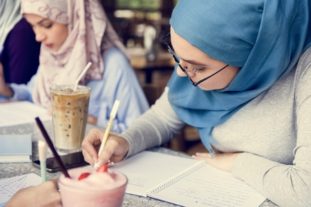 Muslim women writing in a cafe