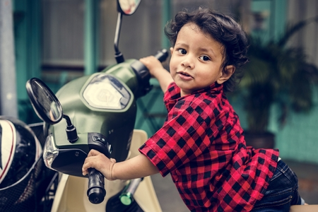Young Indian boy riding the motorbike Imagens