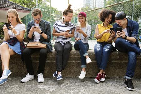 Jonge volwassen vrienden die smartphones samen buitenshuis gebruiken, jeugdcultuurconcept