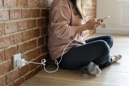 Mujer joven con un teléfono inteligente mientras se carga