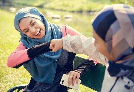 Muslim women giving each other a fist bump
