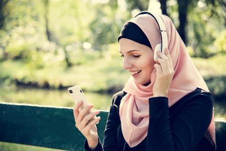 Muslim woman listening to music Imagens