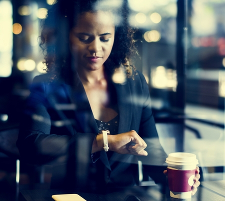 Woman looking at her watch at cafe Banco de Imagens