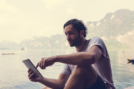 Man using his phone by a lake Stock Photo