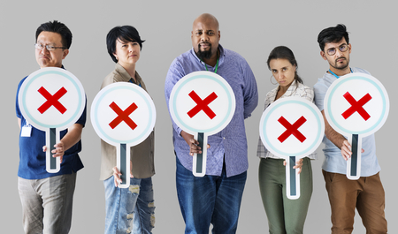Workers standing and holding incorrect tick boxes Stock Photo