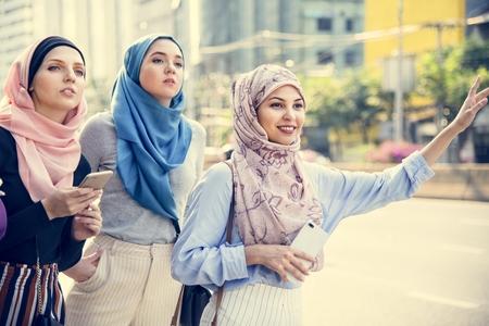 Muslim women hailing a cab 免版税图像 - 116130525