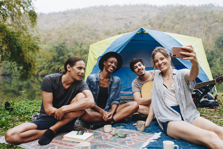Group of young adult friends in camp site taking a group selfie outdoors recreational leisure, freedom and adventure concept Banque d'images - 109643971