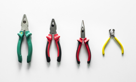 Flat lay of various pliers isolated on white background