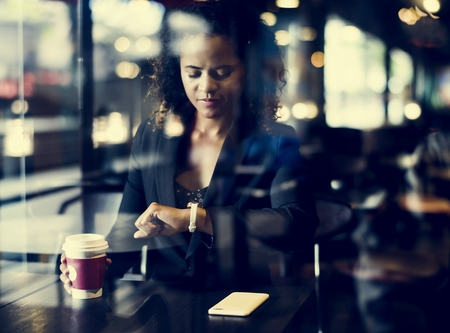 Woman looking at her watch at cafe Stock Photo