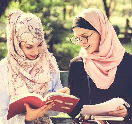 Muslim women reading a book Stock Photo