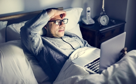 Man using laptop on a bed Stock Photo