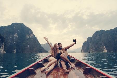 Pareja tomando selfie en un bote de cola larga