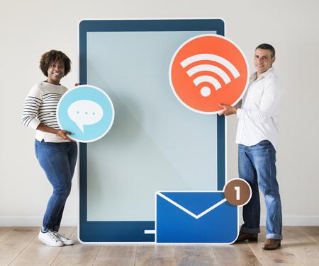 Diverse couple holding a tablet with graphics Foto de archivo - 109644343