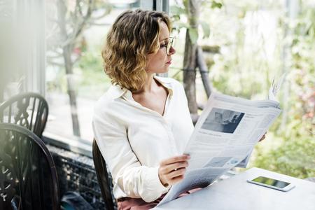 Mujer de negocios leyendo el periódico en la mañana