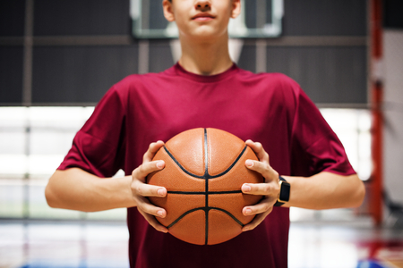 Teenage boy holding a basketball on the court Banco de Imagens