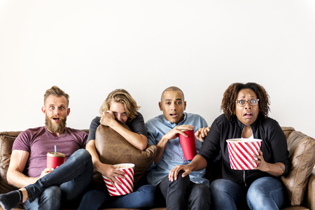 Group of friends terrified watching thriller movie Stock Photo