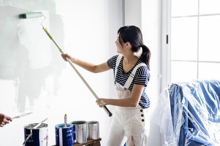 Asian woman panting house wall Standard-Bild - 109887792