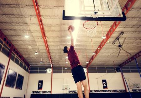 Caucasian teenage boy playing basketball alone on the court Stock Photo