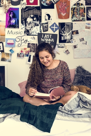 Teenage girl reading a book in a bedroom