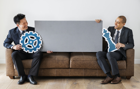 Businessmen sitting together with icons Stock Photo