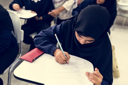 diverse muslim children studying in classroom Imagens