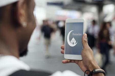 Garçon musulman à l'aide d'un smartphone Banque d'images