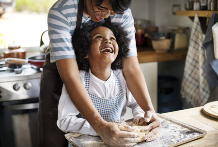 Mother and son kneading dough in the kitchen
