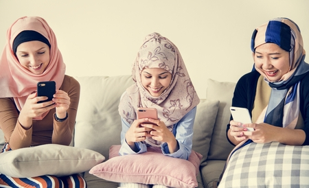Muslim women using their phones