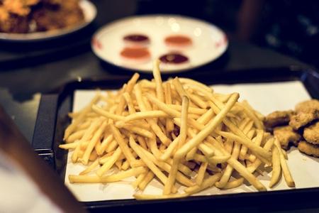 Tablett mit Junk-Food-Fast-Food-Hühnernuggets und Pommes Frites Standard-Bild
