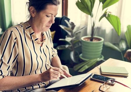 Caucasian woman writing to do list on tablet Stok Fotoğraf