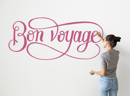Artist woman writing Bon Voyage on the wall