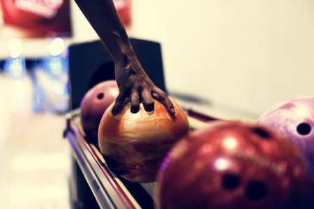 African American boy picking up a bowling ball hobby and leisure concept