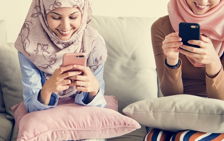Muslim women using phones Stock Photo